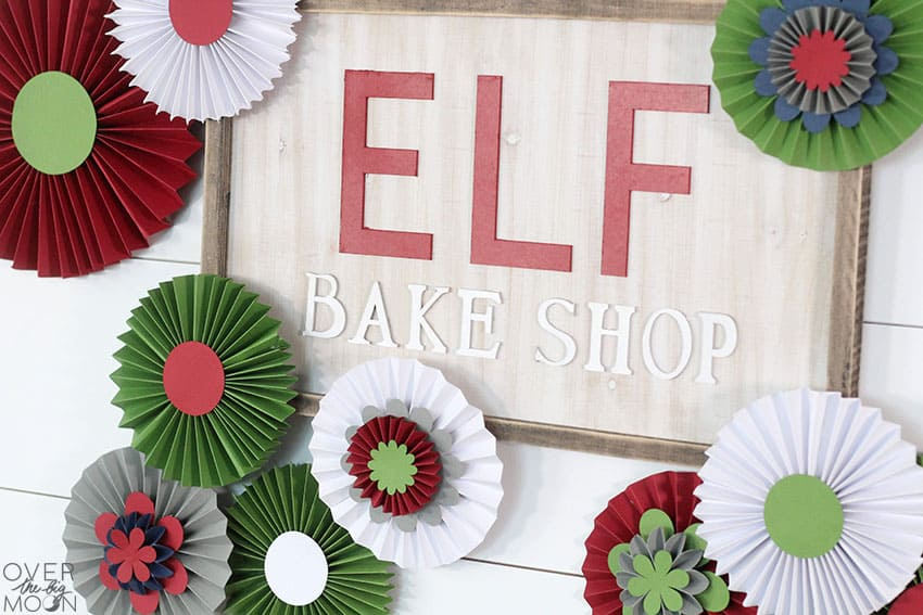 DIY Elf Bake Shop Sign and Rosette Backdrop made with my Cricut Maker! From overthebigmoon.com!