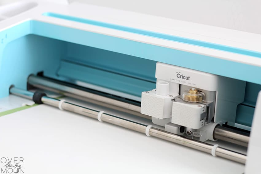 Cricut Maker with Scoring Wheel loaded and scoring Glitter Cardstock! From overthebigmoon.com!