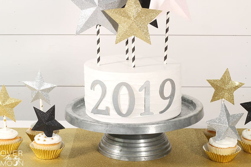 DIY New Years Cake - it's so simple to put together a BEAUTIFUL Cake using a simple white store bought cake and make the cake decorations using my Cricut Maker! From overthebigmoon.com!